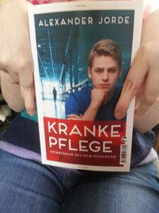 """Hände halten das Buch """"Kranke Pflege"""""""